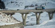 Грузовой трейлер пересекает мост через реку Арагви на Военно-Грузинской дороге