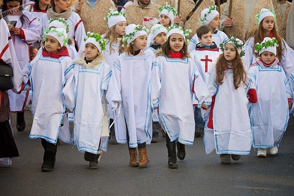 მსვლელობის მთავარი მონაწილეები - თეთრ სამოსში ჩაცმული ბავშვები წითელი ჯვრებით