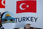 Человек в маске с изображением Купола Скалы принимает участие в проамериканской демонстрации возле Стамбульского конгресс-центра, когда лидеры и представители стран-членов Организации Исламского сотрудничества (ОИК) собираются на внеочередное заседание в Стамбуле, Турция