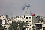 Дым от взрыва подымается над домами в городе Мадера, Сирия
