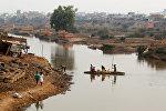 Люди пересекают реку Икопа на лодке близ Антананариву в Мадагаскаре