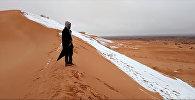Человек смотрит на выпавший снег в пустыне Сахара