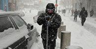 Человек пытается очистить свою машину от снега после снежной бури в Нью-Йорке, США