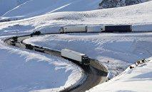 Грузовые трейлеры едут зимой по заснеженной по Военно-Грузинской дороге