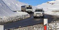 Грузовой трейлер и машина едут по Военно-Грузинской дороге