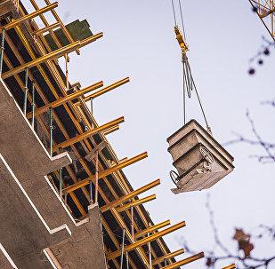 Подъемный кран поднимает груз на строительстве нового многоэтажного жилого дома в грузинской столице