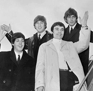 Группа Битлз. На фото (слева направо) - Пол Маккартни, Джон Леннон, Джимми Никол и Джордж Харрисон перед отлетом из Лондона в июне 1964 года, когда они отправляются в турне по Скандинавии. Ринго Старр в то время был болен и его временно заменял барабанщик Джимми Никол