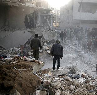 Жители стоят на фоне разбомбленных зданий в городе Гамория, Дамаск, Сирия