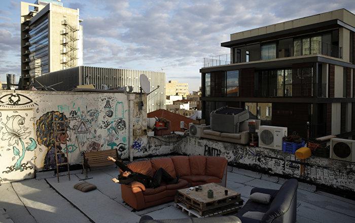 Житель Тель-Авива 26-летний Гай Эльхадад отдыхает на диване на крыше своего дома. Для Гая его крыша - это творческий инкубатор. Как он говорит, на крыше мы можем делать все, что хотим, потому что нам не нужно одобрение других. Он и два соседа по квартире занимаются на крыше йогой, музыкой и искусством. Также они сделали проход через крышу для других жителей и постарались украсить это пространство