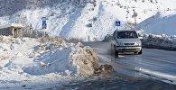 Машина на заснеженной трассе в горах
