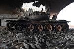 Сожженный танк у военного аэропорта Абу-Духур в провинции Идлиб после боев, в ходе которых сирийская армия восстановила контроль над данным районом
