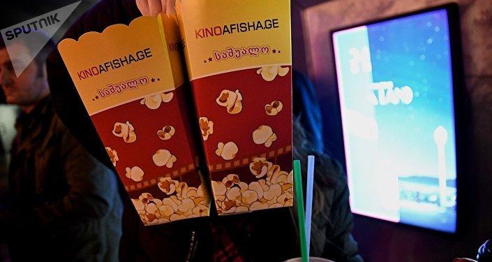 Девочка держит в руках пакеты с попкорном в одном из тбилисских кинотеатров
