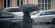 Женщина с зонтиком идет по одной из тбилисских улиц