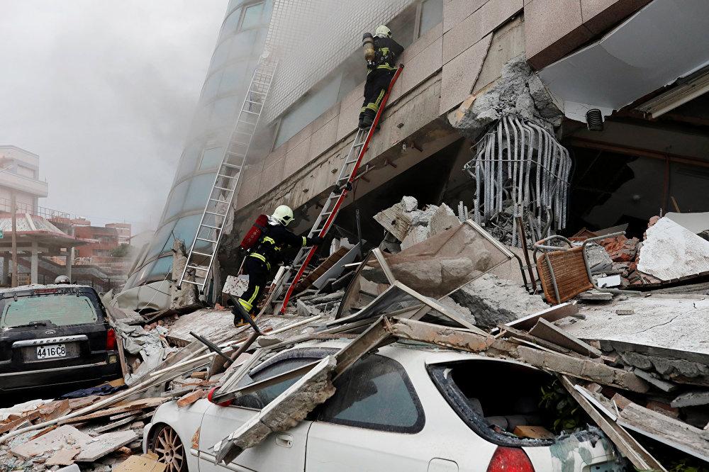 Пожарные пытаются спасти выживших среди руин зПо последним данным, жертвами природной катастрофы стали четыре человека, 225 пострадали, 140 человек не выходят на связь. На фото - пожарные пытаются спасти выживших среди руин здания после землетрясениядания после землетрясения на Тайване