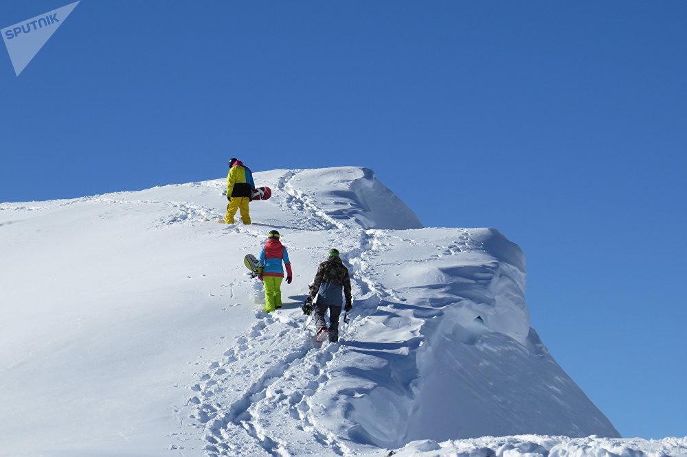 Туристы  поднимаются в гору для спуска на сноубордах
