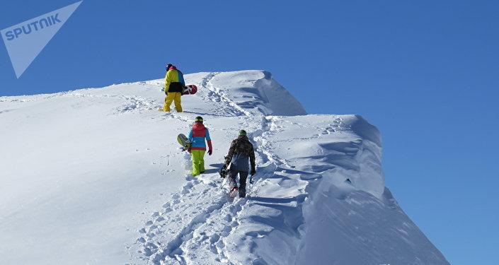 Горнолыжный курорт в Сванетии - Туристы поднимаются в гору для спуска на сноубордах