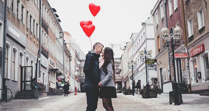 Влюбленная пара держит воздушные шарики в виде сердечек