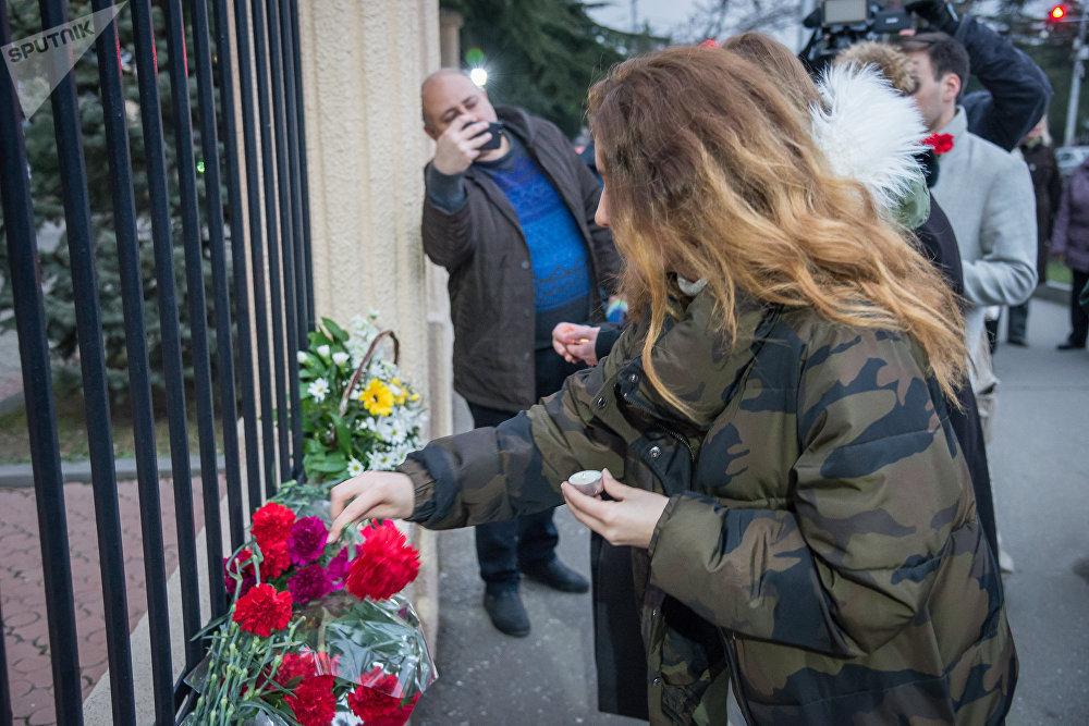 Люди, которые пришли в этот день, чтобы выразить свою скорбь, возлагали цветы и зажигали свечи у ограды здания Секции интересов РФ