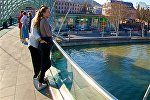 Туристы смотрят на Тбилиси с моста Мира в центре грузинской столицы