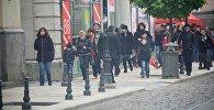 Люди идут по одной из улиц столицы Грузии осенним утром