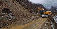 Спецмашина расчищает дорогу от оползня на дороге