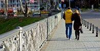 Молодая пара гуляет по Метехскому мосту в центре Тбилиси