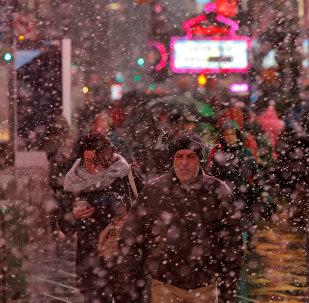 Люди идут по Таймс-сквер в Нью-Йорке во время мартовского снегопада