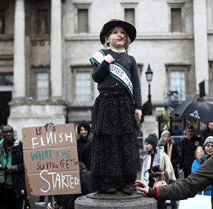 Маленькая девочка, одетая как суфражистка (участница движения за предоставление женщинам избирательных прав), во время мероприятия March4Women в центре Лондона. Суфражистки в конце XIX - начале XX веков выступали против дискриминации женщин в политической и экономической жизни