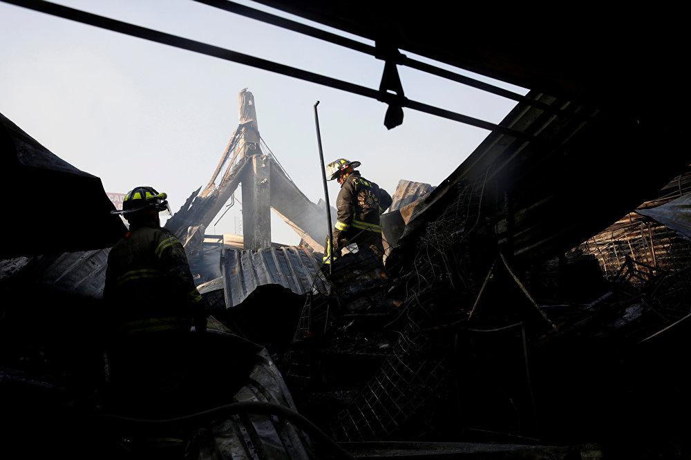 Пожарные занимаются ликвидацией очагов возгорания после сильного пожара на рынке Мигеля Идальго, который уничтожил большую часть здания, в Мехико, Мексика