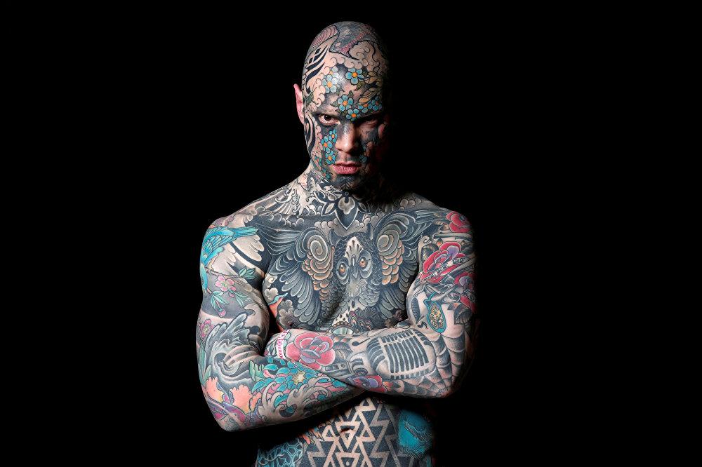Сильвен, школьный учитель и модель из Франции, позирует фотографу на тату-шоу Le Mondial du Tatouage в Париже, Франция
