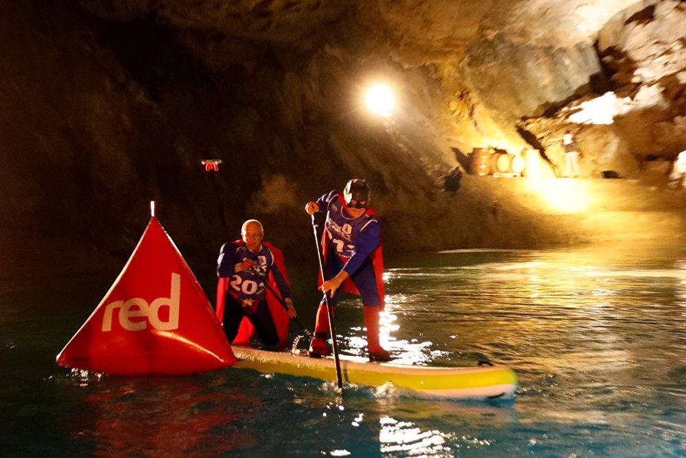 Спортсмены в костюмах супергероев во время гонок Alpine Lakes Tour на крупнейшем в Европе подземном озере Сен-Леонар, Швейцария