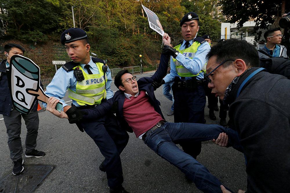 Полиция задерживает одного из участников акции протеста против дисквалификации законодателей перед тем, как глава администрации Гонконга Кэрри Лам должен прибыть на голосование во время выборов в местный законодательный совет