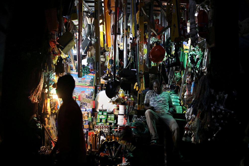 Продавец сидит внутри своей лавки среди многих подобных на улице Порт-о-Пренс, Гаити