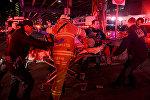 Представители чрезвычайных служб эвакуируют пострадавших с места падения вертолета в Нью-Йорке, США