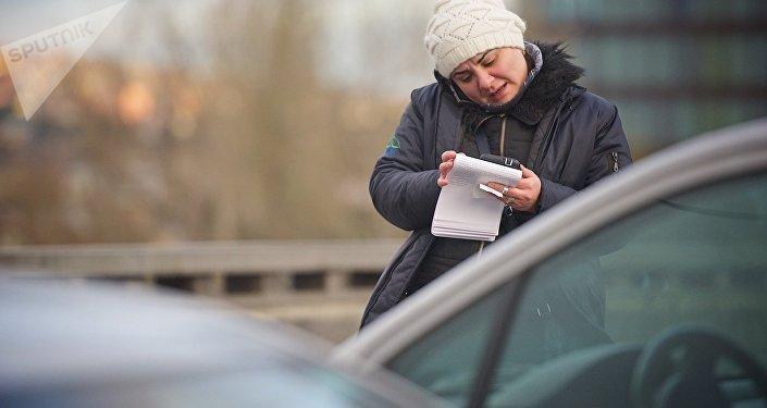 Работник CT Park выписывает штраф за нарушение правил парковки