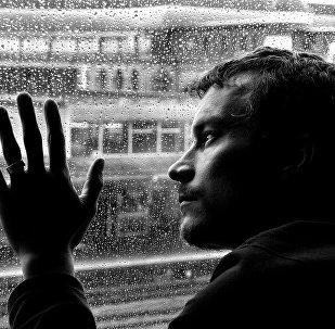 ნაღვლიანი მამაკაცი ნაწვიმარი ფანჯრის ფონზე