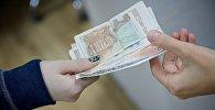 Люди передают друг другу купюры грузинской валюты лари различного номинала