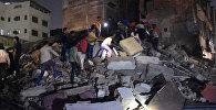 Спасатели и местные жители ищут оставшихся в живых среди руин на месте обрушившегося здания отеля в городе Индаур, Индия