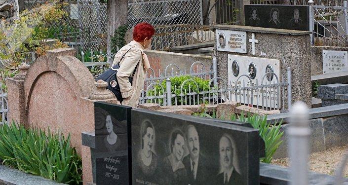 Женщина идет по Кукийскому кладбищу среди могил